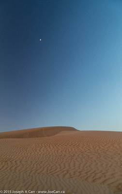 Half phased Moon over the sand dunes after sunrise