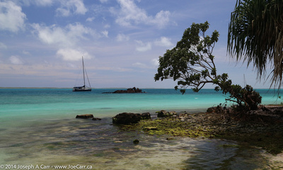 Sailboat moored and small shipwreck in the lagoon
