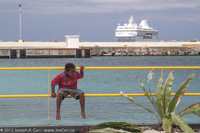 Little boy sitting on the rail with the ship behind