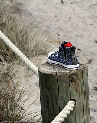 A forgotten kid's runner and red sock on a post beside the trail to the beach