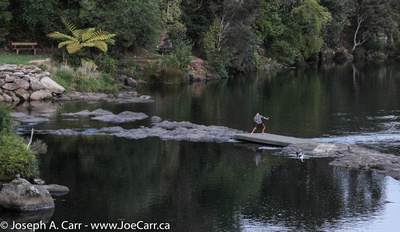 Boy playing on the Kerikeri River downstream from the pedestrian bridge
