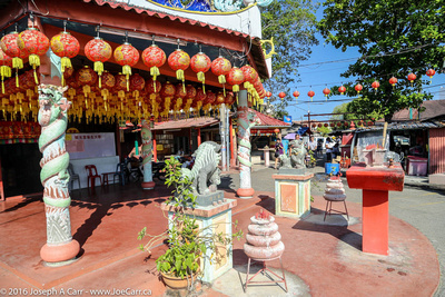 A street temple decorated for Lunar New Year with incense and joss sticks