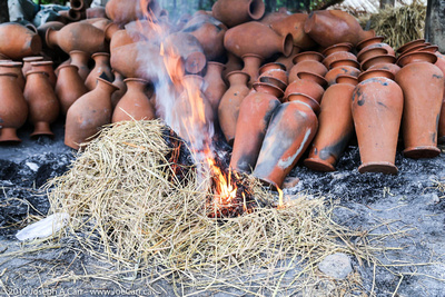Pots in burning rice straw