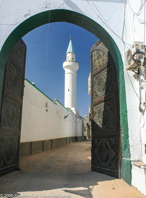 Minaret tower framed by arched entrance and bronze doors leading to a Tripoli back street