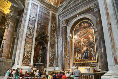 People worshiping in a chapel with a statue of a pope beside and painting in front