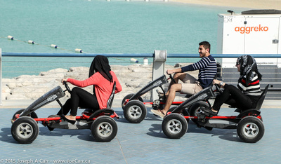 Young people riding go carts along the harbour promenade