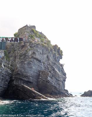Sunbathers on a steep-sloped rock below a Vernazza cliff top resort
