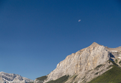 The old Moon at Noon over the south end of Mt. Rundle