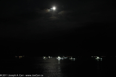 Tuna fishing fleet at anchor under a Full Moon
