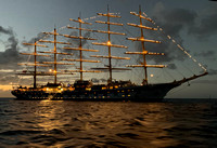The Royal Clipper masts lit at sunset while at anchor in the harbour