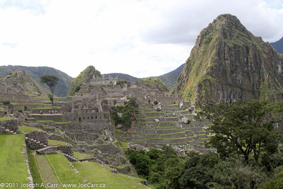 Classic photo of Machu Picchu showing the agricultural terraces, temples and living areas, and Cerro Huayna Picchu (Temple of the Moon)