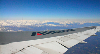 Snow-covered Italian Alps with Alitalia aircraft wing