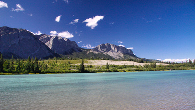 A kayaker on the Bow River with the Rocky Mountains (Mount Yamnuska)