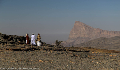 Our drivers huddled against the cold wind with Jebel Misht in the distance