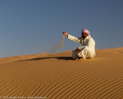 Arab man sitting on a sand dune