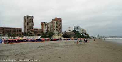 Beach umbrellas & people on the beach with towers behind
