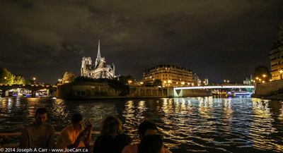 Notre Dame lit at night where  Île de la Cité splits the Seine River