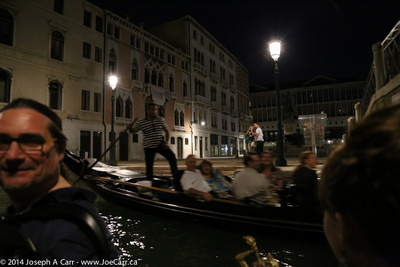 Gondolas passing on a canal at night