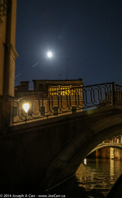 A bridge over a canal with the Full Moon behind