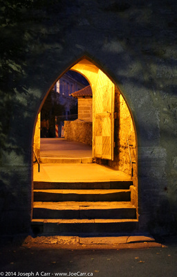 Archway and gate lit at night