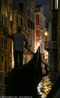 Gondoliier and gondola on a canal at night