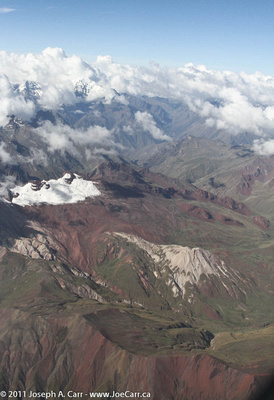 Green and red hills with snow-capped Andes Mountains