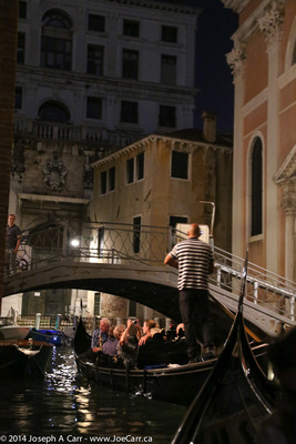 Our group in a gondola passing under a bridge on a canal at night