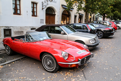 High end cars parked in the street, including a classic Jaguar