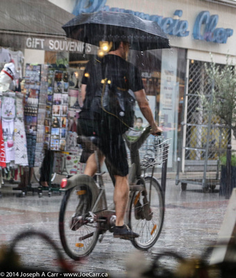 Cyclist holds an umbrella while riding a  Vélib bike in the rain