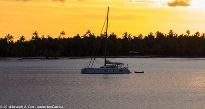 A sailboat shelters in a bay as the Sun sets south of Bora Bora