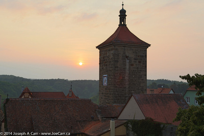 Tower, rooftops and the setting sun