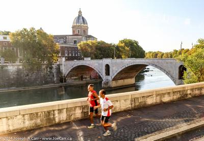 Joggers run beside the Tiber River