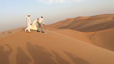 Our guide Kais rides a snowboard down a sand dune