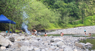 Tahitians having a BBQ and swimming in the river