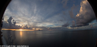 Sunset south of Bora Bora and a funnel cloud to the north (right)