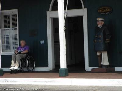 A wooden captain and a sleeping man (in his wheelchair) at the entrance to the Pioneer Inn
