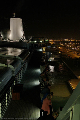 Passengers on Sport Deck watch Volendam pull away from the dock