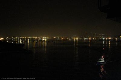 Pilot boat escorts Volendam through Noumea harbour during night departure