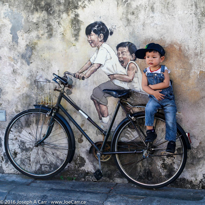 A boy sitting on street art - Kids on bicycle by Earnest Zacharevic