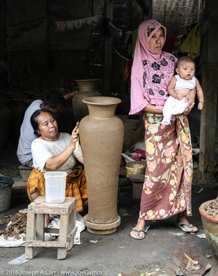 Woman making a tall pot with a younger woman holding a baby