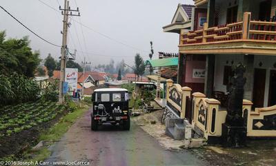 Jeeps descending through a village