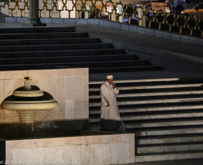 An Omani man on the steps of the Al-Zawawi Mosque at night