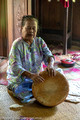 Woman singing and playing the drum in the Melayu longhouse