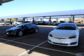 A white Model S 90D parked beside my Model S75D under the solar canopy