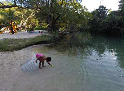 Jamaican girl playing in the freshwater stream