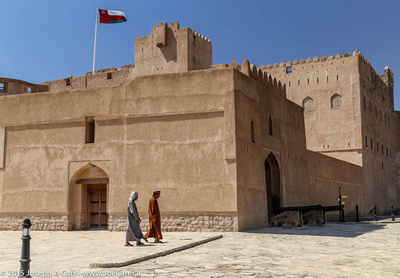 Two Arab men walk by the castle