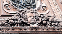 A cherub carved into a big door outside the Louve