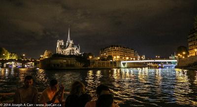 Notre Dame lit at night where  Île de la Cité splits the Seine River