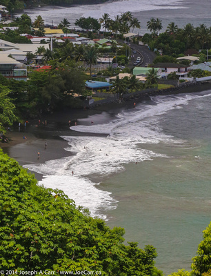 Swimmers on a black sand beach in Mataval Bay