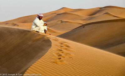 Arab man on a windswept sand dune